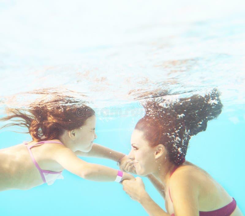 Família de sorriso feliz debaixo d'água na piscina fotografia de stock royalty free