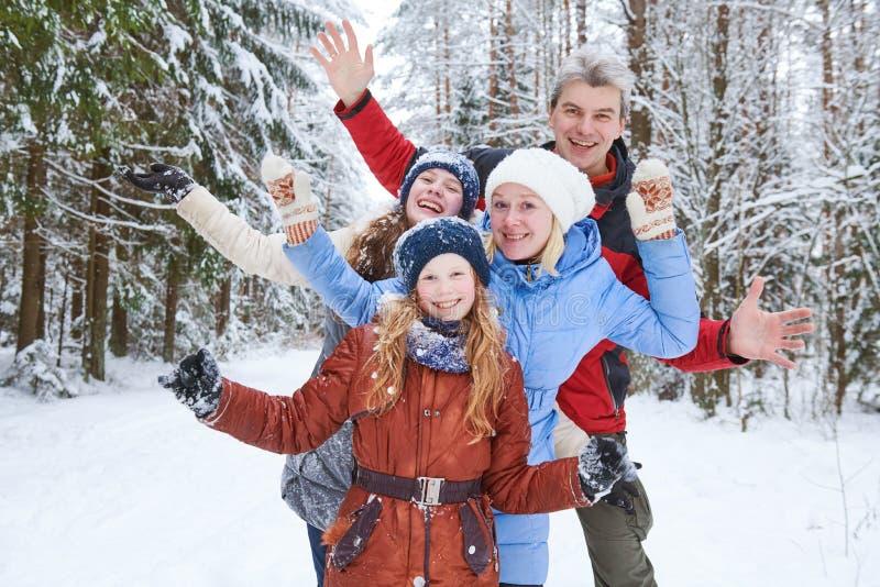 Fam?lia de sorriso feliz na floresta nevado do inverno imagens de stock royalty free