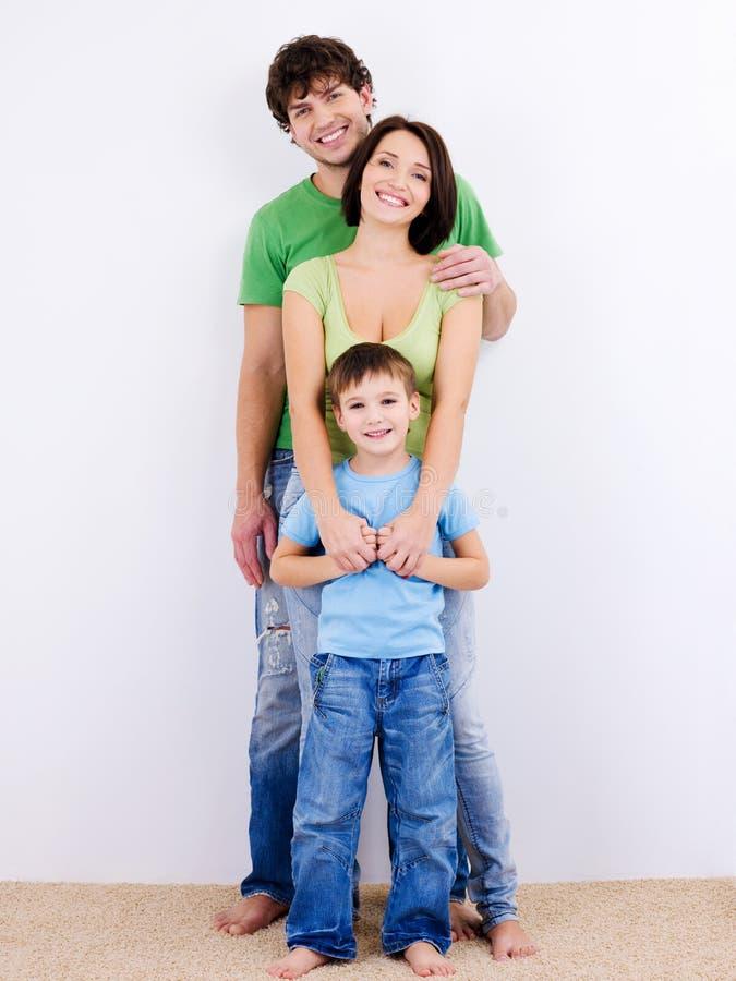 Família de sorriso feliz nova que olha a câmera fotos de stock
