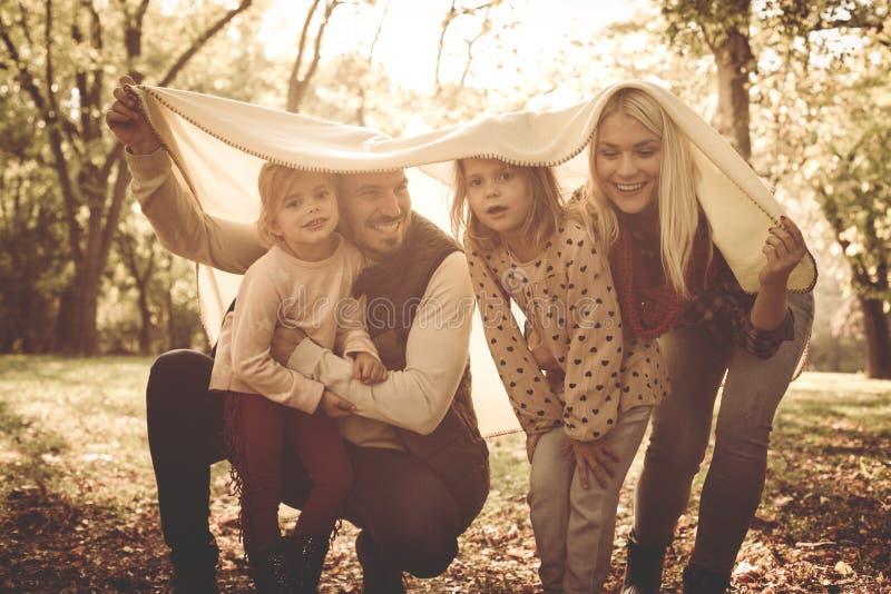 Família de sorriso feliz que joga no parque com cobertura imagem de stock