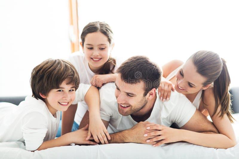 Família de sorriso na cama fotografia de stock royalty free