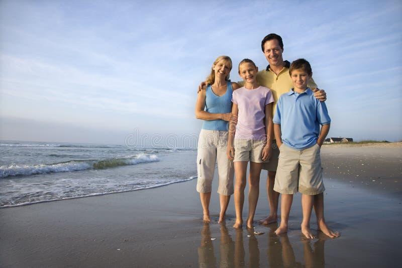 Família de sorriso na praia.