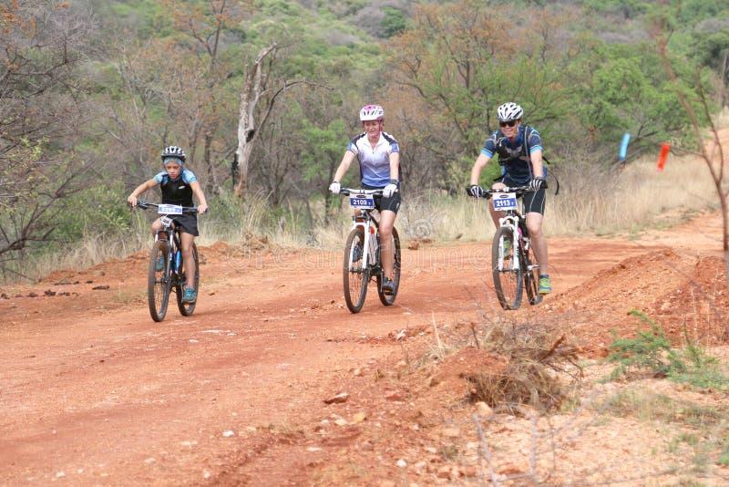 Família de sorriso que aprecia fora o passeio na raça do Mountain bike fotos de stock