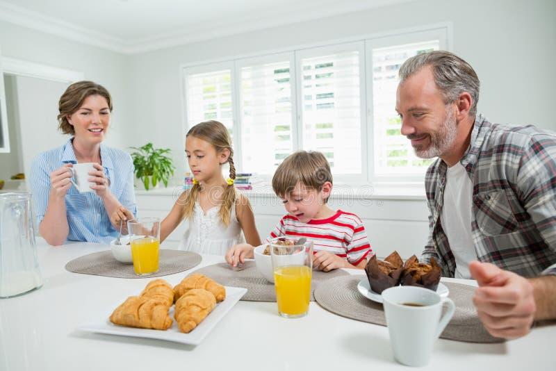 Família de sorriso que come o café da manhã na cozinha fotos de stock