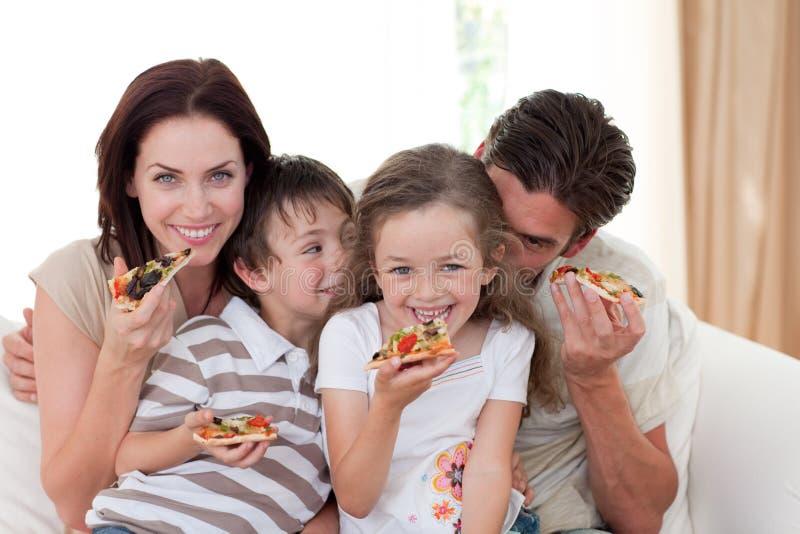 Família de sorriso que come a pizza fotografia de stock