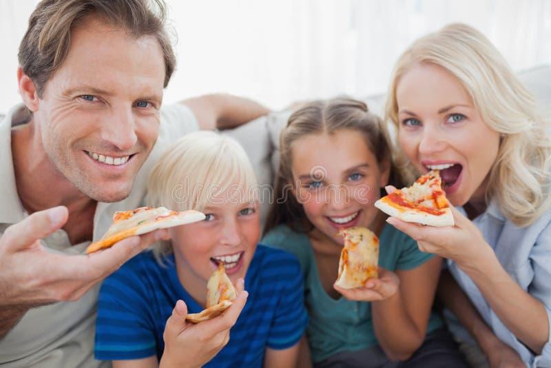 Família de sorriso que come a pizza foto de stock royalty free