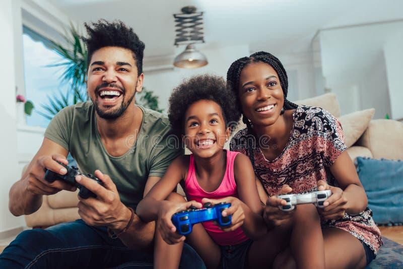 Família de sorriso que senta-se no sofá que joga jogos de vídeo fotografia de stock