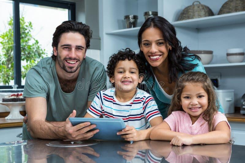 Família de sorriso que usa a tabuleta na cozinha imagens de stock royalty free