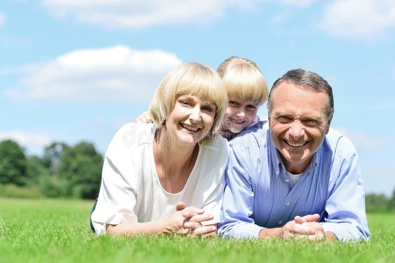 Família de três adorável que encontram-se no parque foto de stock