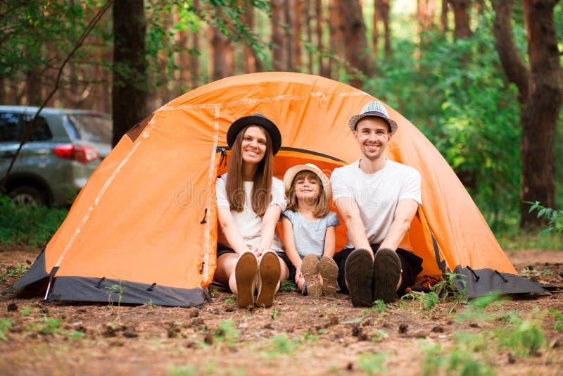 Família de três feliz em uma viagem de acampamento que relaxa imagens de stock