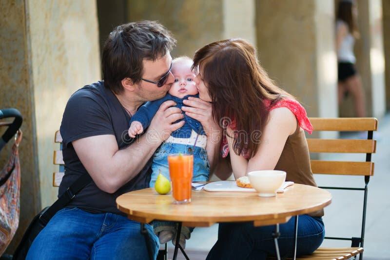 Família de três feliz que comem o café da manhã imagem de stock