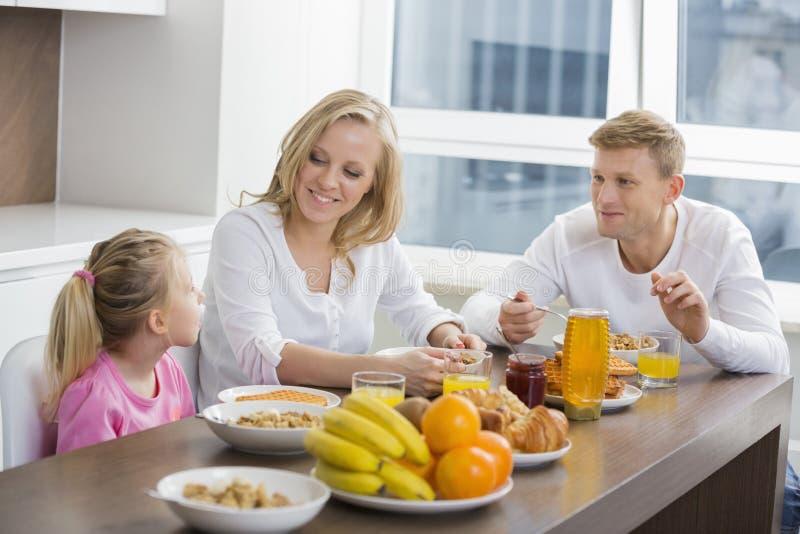 Família de três feliz que comem o café da manhã na tabela imagens de stock