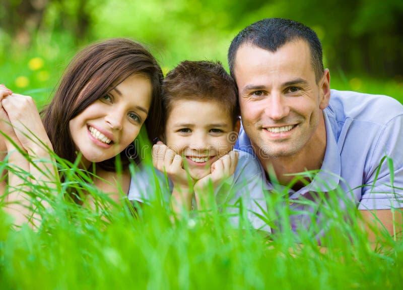 Família de três feliz que encontram-se na grama imagem de stock