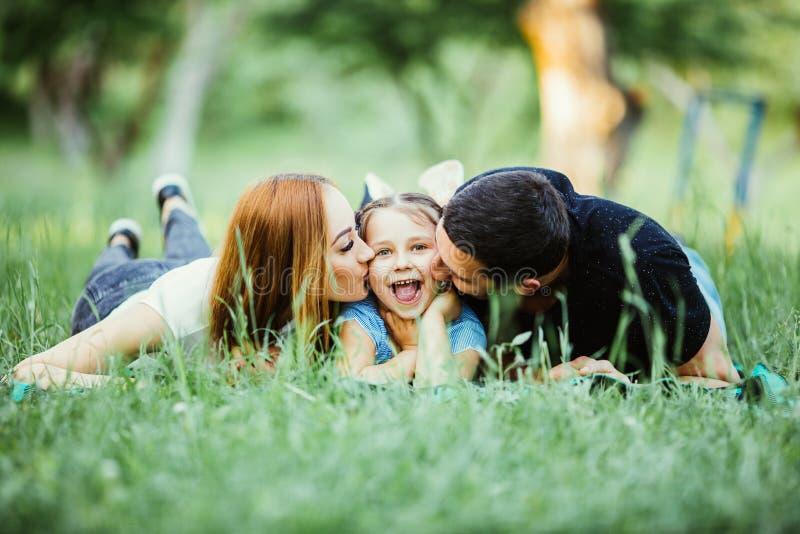Família de três feliz que encontram-se na grama no parque do verão fotos de stock royalty free