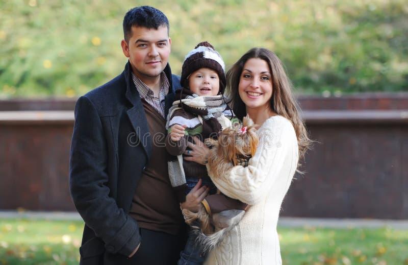 Família de três feliz que estão junto no parque no outono foto de stock