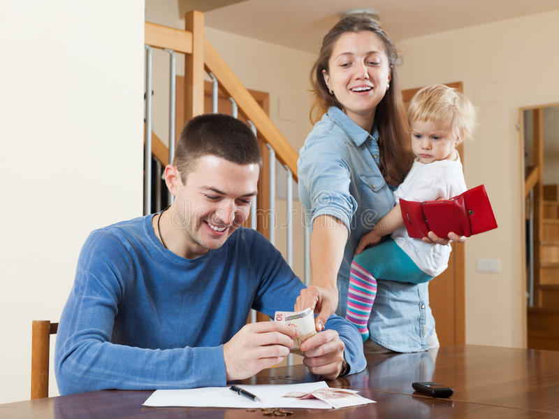 Família de três feliz que racham o dinheiro fotografia de stock