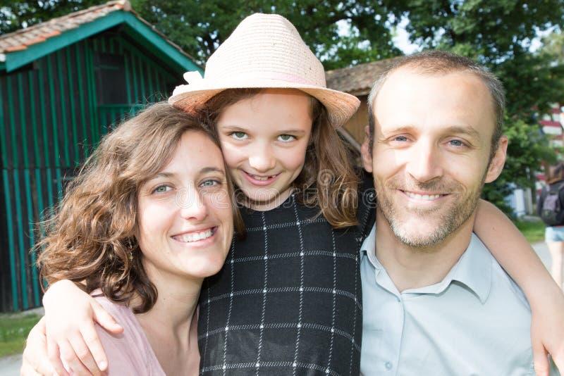 Família de três feliz que têm a filha pequena do divertimento junto fora com o pai da mãe do abraço do chapéu foto de stock royalty free