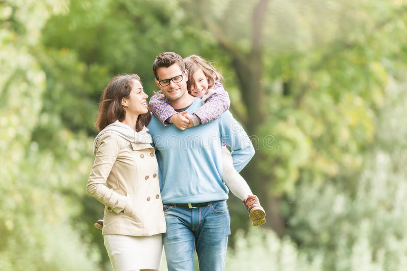 Família de três feliz que têm o divertimento exterior. fotos de stock