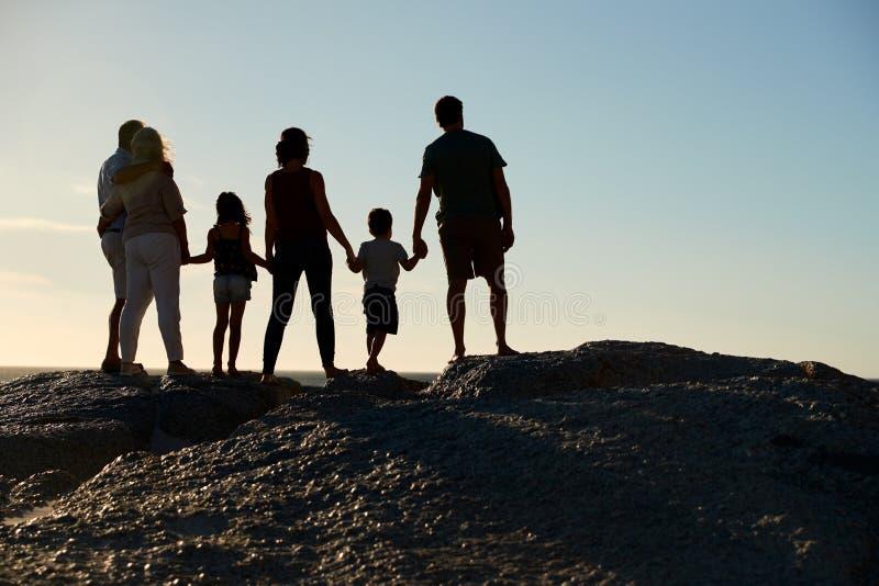 Família de três gerações em uma praia que guarda as mãos, admirando a vista, comprimento completo, silhueta, vista traseira fotografia de stock