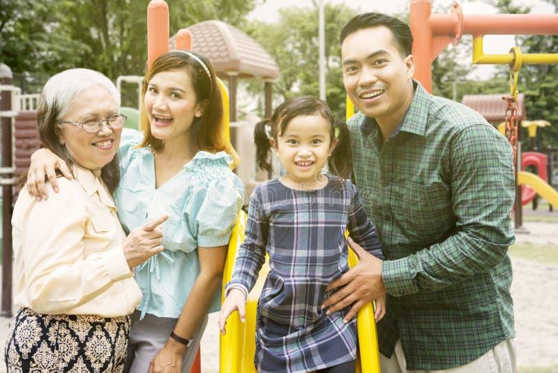 A família de três gerações olha feliz no campo de jogos imagem de stock