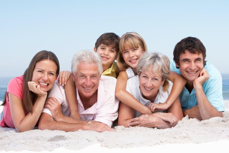Família de três gerações que relaxa na praia fotos de stock
