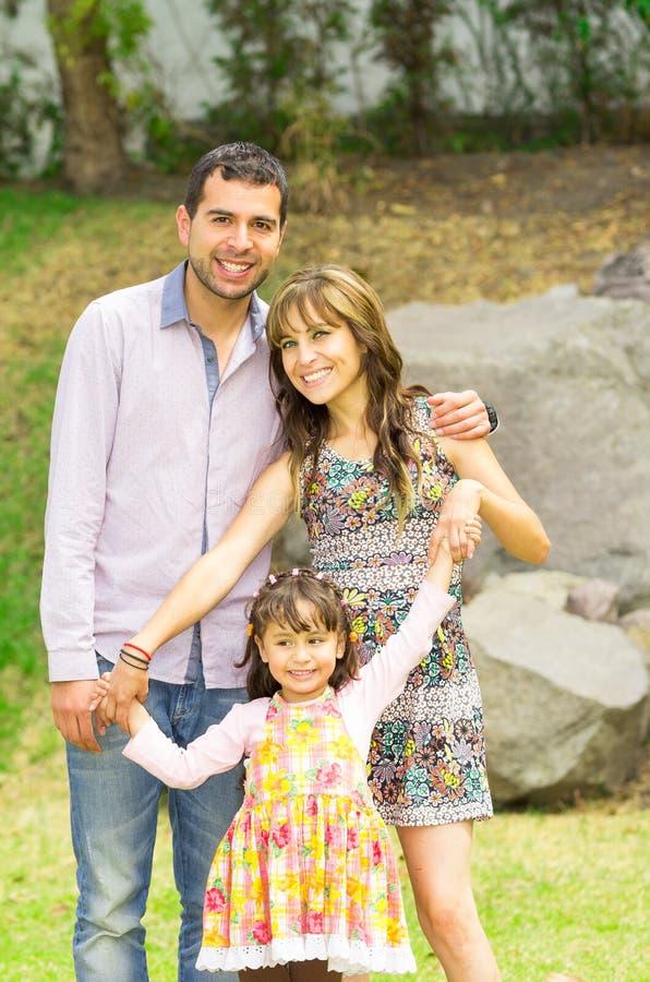Família de três latino-americano adorável que levantam no jardim fotos de stock