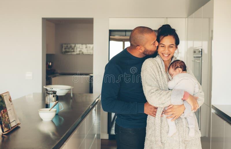Família de três nova bonita na cozinha imagens de stock royalty free