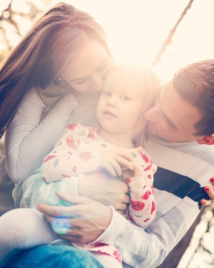 Família de três nova que têm o divertimento em um parque que aprecia seu tempo junto Povos reais, conceito da autenticidade imagens de stock royalty free