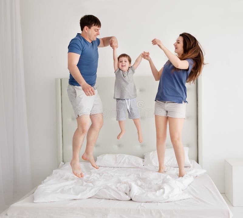 Família de três, pais novos e um filho pequeno que salta e que tem o divertimento na cama fotografia de stock