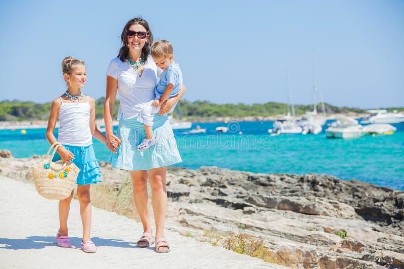 Família de três que anda ao longo da praia tropical imagens de stock
