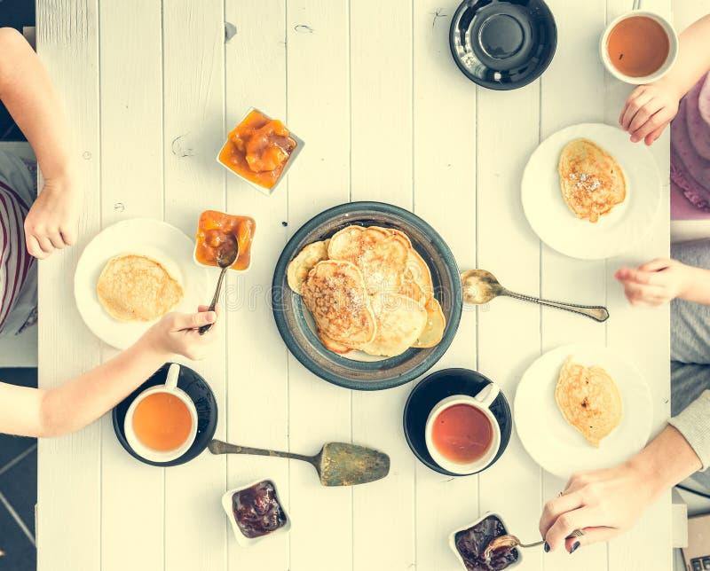 Família de três que comem o café da manhã