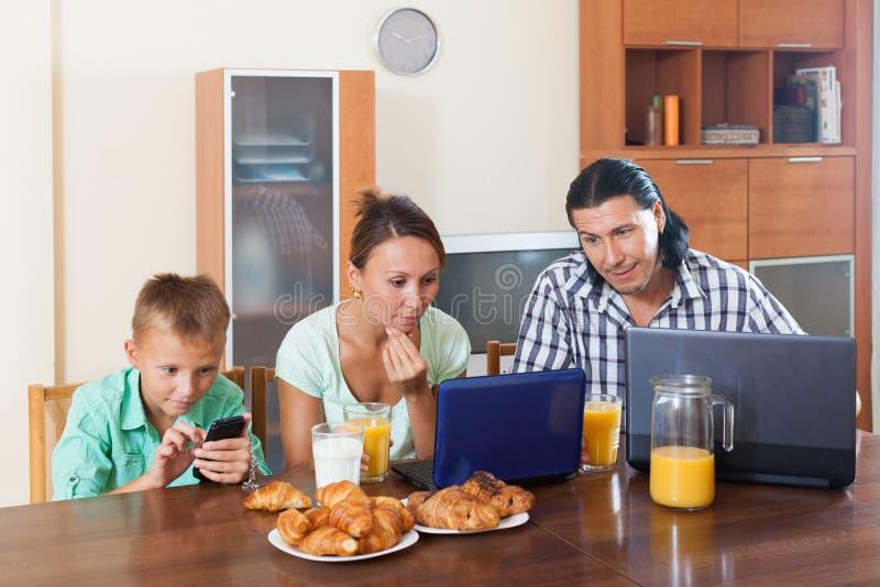 Família de três que comem o café da manhã em casa fotografia de stock royalty free