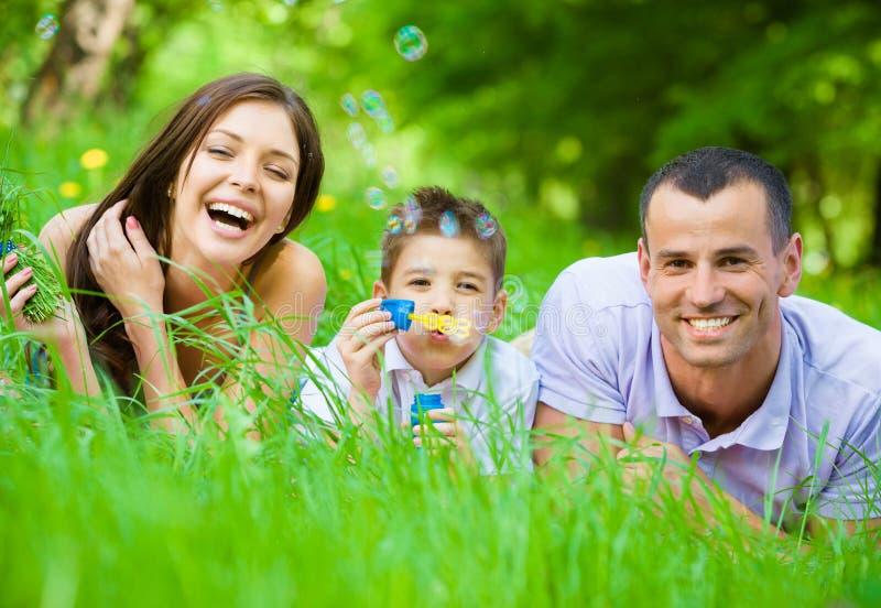 A família de três que encontram-se na grama e nos sopros borbulha imagem de stock