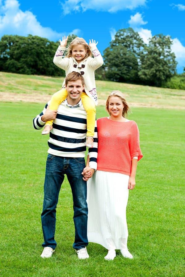 Família de três que levantam de encontro ao fundo natural fotos de stock royalty free