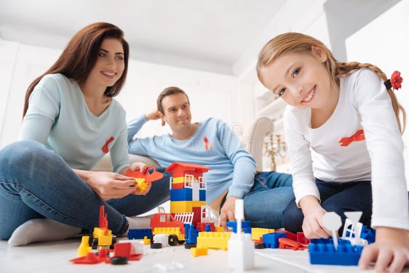 Família deleitada alegre que senta-se em torno do grupo do meccano foto de stock