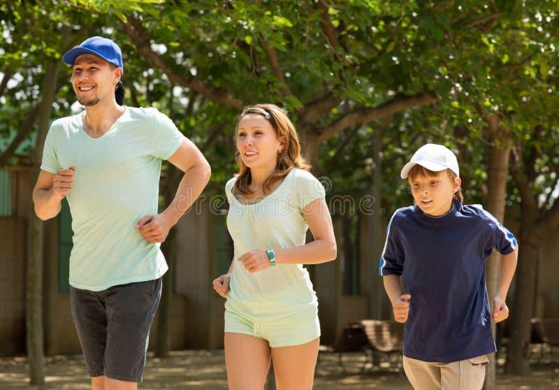 Família desportivo com o filho que corre no parque fotografia de stock royalty free