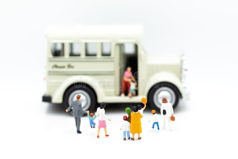 Família diminuta: Os pais estão indo enviar crianças ao ônibus para vão à escola Uso da imagem para o conceito da educação foto de stock royalty free