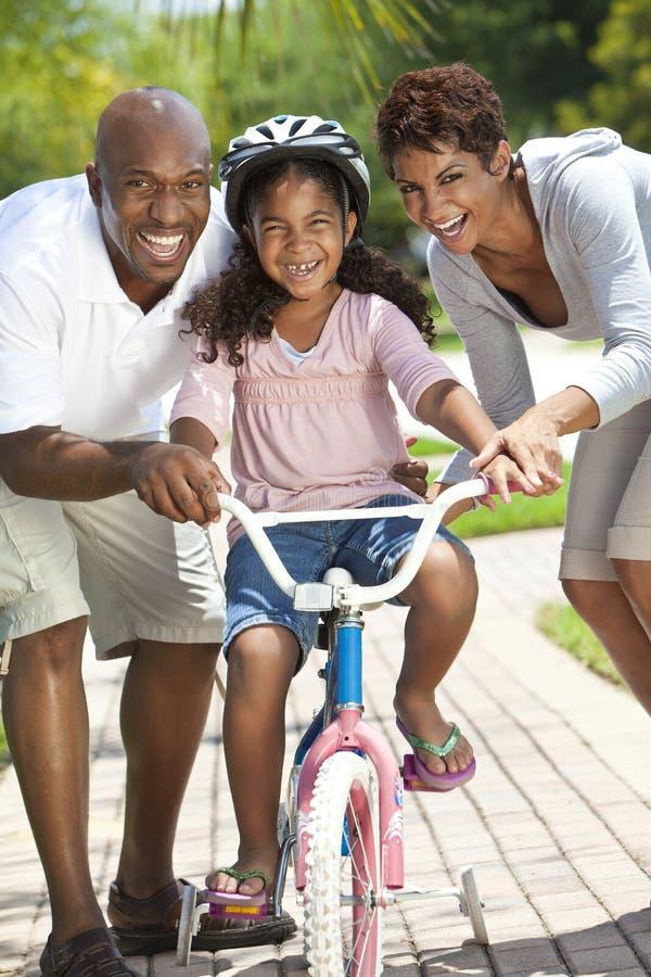 Família do americano africano & bicicleta felizes da equitação da menina fotografia de stock
