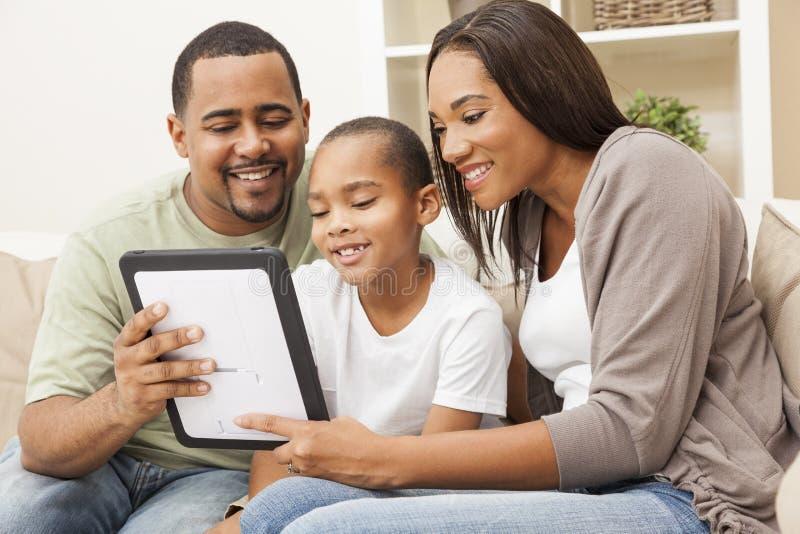 Família do americano africano que usa o computador da tabuleta