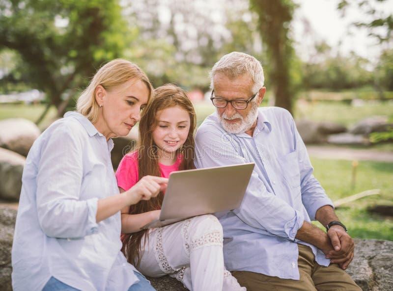 Família do avô e dos netos que usa o portátil ao descansar no parque foto de stock