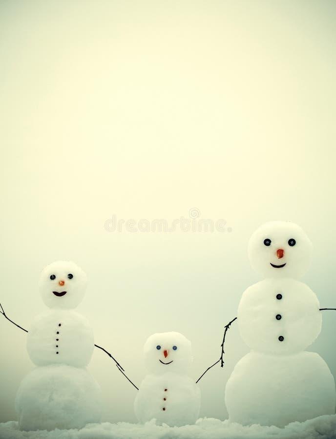 Família do boneco de neve no fundo vermelho Mãe, pai e criança do ano novo da neve fotografia de stock