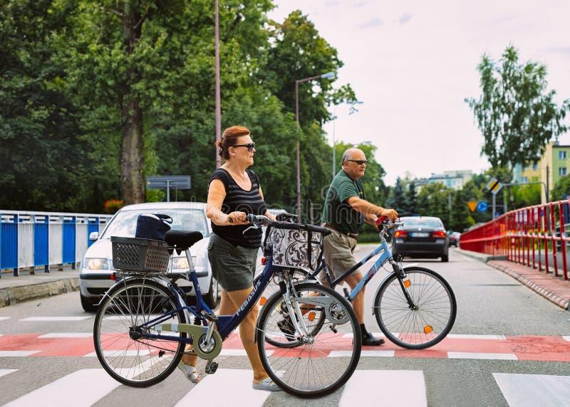 Família do homem superior e da mulher nas bicicletas que cruzam a rua em Varsóvia, Polônia fotos de stock