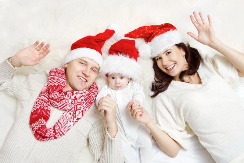 Família do Natal com o bebê em chapéus vermelhos. imagens de stock royalty free
