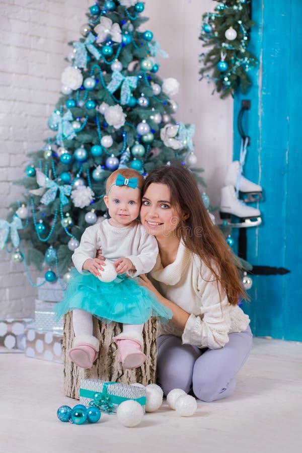 Família do Natal na casa acolhedor caseiro que levanta perto da árvore de novo-ano colorida no azul Mulher bonita com a filha bon foto de stock royalty free