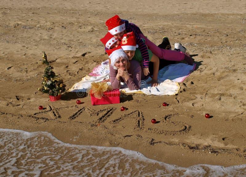 Família do Natal que coloca na praia 1 da areia foto de stock royalty free