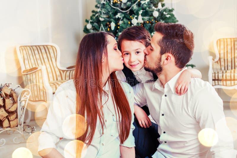 Família do Natal que sorri e que beija perto da árvore do Xmas Sala de visitas decorada pela árvore de Natal e pela caixa de pres imagem de stock