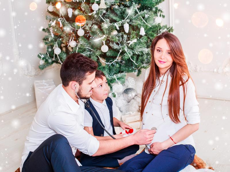 Família do Natal que sorri e que beija perto da árvore do Xmas Sala de visitas decorada pela árvore de Natal e pela caixa de pres fotografia de stock royalty free