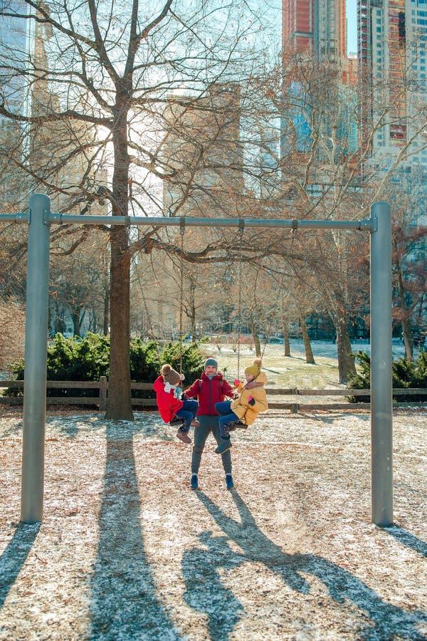 A família do pai e as crianças no Central Park têm o divertimento em férias americanas em New York imagem de stock royalty free