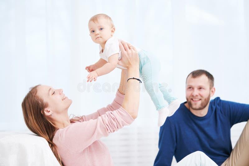 Família do Parenting Mãe e pai que jogam com o bebê recém-nascido pequeno foto de stock