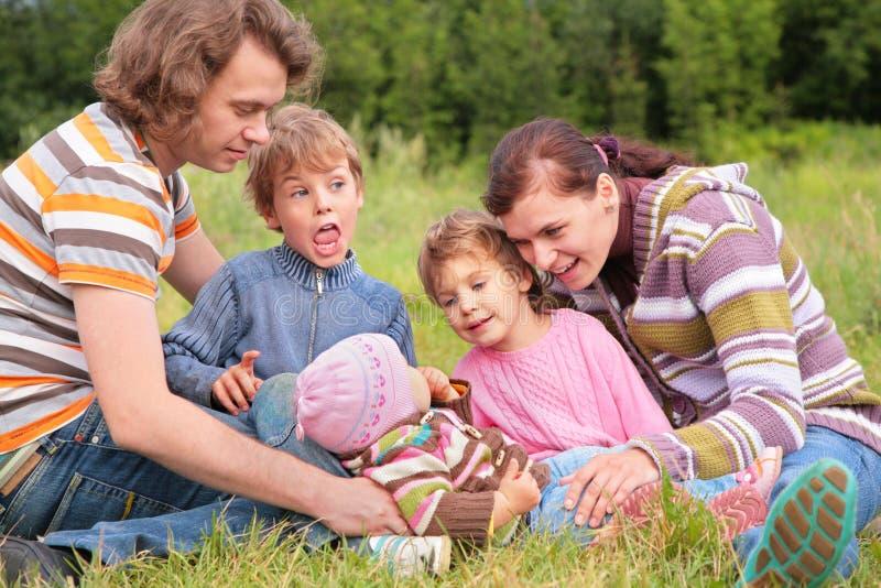 Família do retrato cinco na grama imagens de stock